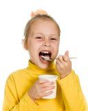 Chica joven que come el yogur Imagenes de archivo