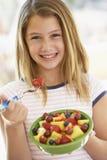 Chica joven que come la ensalada de fruta fresca Imágenes de archivo libres de regalías
