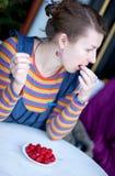 Chica joven que come la frambuesa Imagen de archivo
