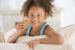 Chica joven que come la galleta en la sonrisa de la sala de estar imagen de archivo libre de regalías