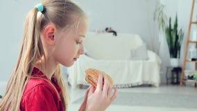 Chica joven que come la hamburguesa metrajes