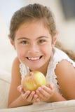 Chica joven que come la manzana en la sonrisa de la sala de estar Fotografía de archivo