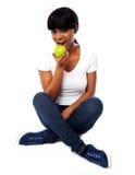 Chica joven que come la manzana verde fresca Fotos de archivo