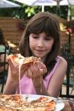 Chica joven que come la pizza Imagenes de archivo