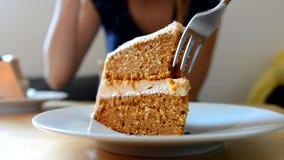 Chica joven que come la torta de la calabaza en el café metrajes