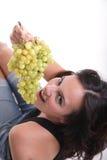 Chica joven que come las uvas Foto de archivo libre de regalías