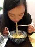 Chica joven que come los tallarines japoneses del Udon Foto de archivo