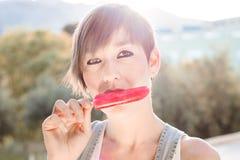 Chica joven que come un polo del helado Foto de archivo libre de regalías