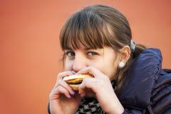 Chica joven que come una hamburguesa Imagen de archivo libre de regalías