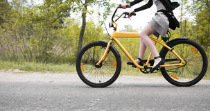 Chica joven que completa un ciclo en la bici de encargo Foto de archivo libre de regalías