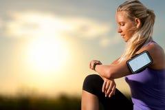 Chica joven que comprueba entrenamiento en el reloj elegante en la puesta del sol imagen de archivo