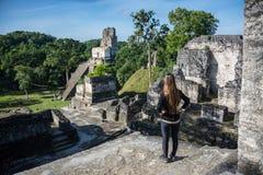 Chica joven que comtempla ruinas mayas en Tikal, parque nacional Tr Fotografía de archivo libre de regalías