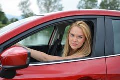 Chica joven que conduce el coche rojo Imagen de archivo