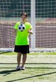 Chica joven que consigue golpear el balón de fútbol con el pie Fotos de archivo
