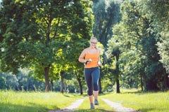 Chica joven que corre abajo de una trayectoria en prado con pesas de gimnasia del peso foto de archivo
