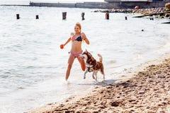 Chica joven que corre en la playa con el perro Fotografía de archivo libre de regalías