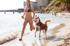 Chica joven que corre en la playa con el perro Foto de archivo