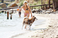 Chica joven que corre en la playa con el perro Fotos de archivo