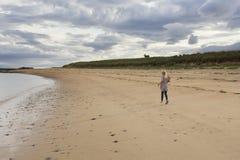 Chica joven que corre a lo largo de una playa imagen de archivo libre de regalías