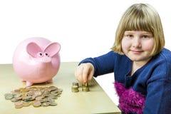 Chica joven que cuenta monedas euro de la hucha Foto de archivo