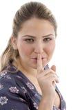 Chica joven que da instrucciones para mantener silencioso Fotografía de archivo