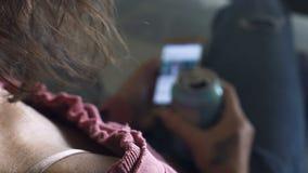 Chica joven que descansa sobre el sofá con la lata de cerveza y el smartphone, forma de vida sedentaria almacen de video