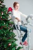 Chica joven que desempaqueta la decoración de la Navidad Foto de archivo libre de regalías