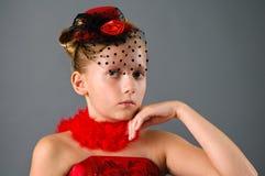 Chica joven que desgasta el pequeño sombrero que presenta en estudio Imagen de archivo libre de regalías
