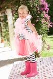 Chica joven que desgasta la boa rosada de Wellington y de pluma Foto de archivo libre de regalías