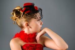 Chica joven que desgasta la pequeña presentación del sombrero negro Imagenes de archivo
