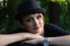 Chica joven que desgasta un sombrero negro Foto de archivo libre de regalías