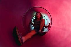 Chica joven que desliza abajo la diapositiva del tubo Fotografía de archivo