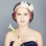 Chica joven que detiene a Lily Flower Elegancia linda de Boho de la cara y del bohemio imagenes de archivo