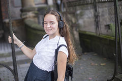 Chica joven que disfruta de música en auriculares en la calle Feliz Fotografía de archivo