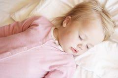 Chica joven que duerme en cama fotos de archivo