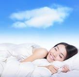 Chica joven que duerme en una almohadilla con la nube blanca Imagen de archivo