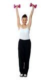 Chica joven que ejercita con pesas de gimnasia Fotos de archivo