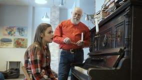 Chica joven que el ` t del doesn consigue jugar bien en el piano, el abuelo la calma abajo almacen de metraje de vídeo