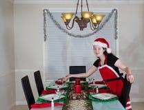 Chica joven que elabora la mesa de comedor para la cena de la Navidad Imagen de archivo libre de regalías