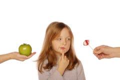 Chica joven que elige entre una manzana y un caramelo Foto de archivo libre de regalías