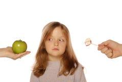 Chica joven que elige entre una manzana y un caramelo Imagenes de archivo