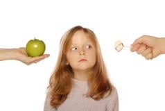 Chica joven que elige entre una manzana y un caramelo Fotografía de archivo
