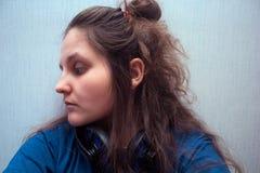 Chica joven que empolla con los auriculares Imágenes de archivo libres de regalías