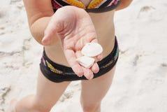 Chica joven que encuentra shelles Fotos de archivo libres de regalías