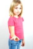 Chica joven que entrega monedas Foto de archivo libre de regalías