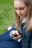 Chica joven que envía un texto mientras que se sienta en la hierba Fotografía de archivo