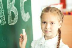 Chica joven que escribe ABC en la pizarra verde Fotografía de archivo libre de regalías