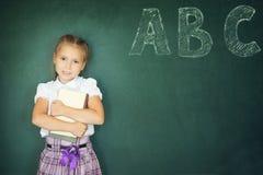 Chica joven que escribe ABC en la pizarra verde Fotografía de archivo