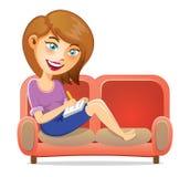 Chica joven que escribe un libro en el sofá Imagen de archivo libre de regalías