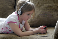 Chica joven que escucha el MP3 Imagen de archivo